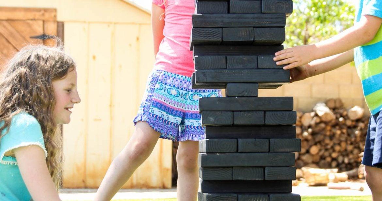 Kids Playing Giant Jenga-inspired Stacking Blocks - DIY Backyard Games plans from @HomeDepot via @PagingSupermom